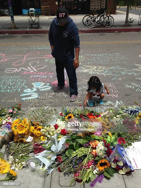 A father and child look at the makeshift memorial in front of the IV Deli Mart in Isla Vista California At this deli is where Elliot Rodger shot and...