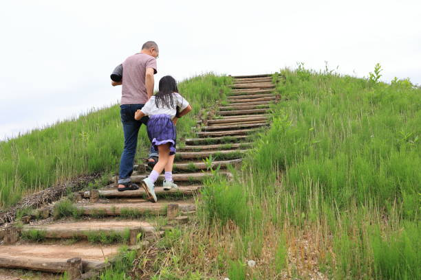 Father and Child Moving Up Together Upstair surrounded by Grass