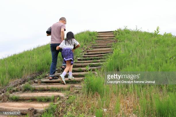 father and child moving up together upstair surrounded by grass - 茨城県 ストックフォトと画像