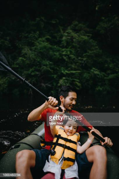 Father and child paddling a raft together