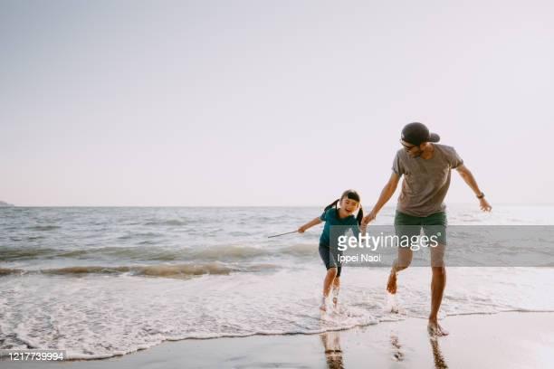 father and child running on beach - travel ストックフォトと画像