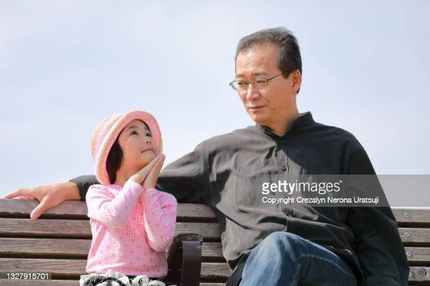 father and child sitting together on a bench outdoor child day dreaming pose - saitama prefecture stock pictures, royalty-free photos & images