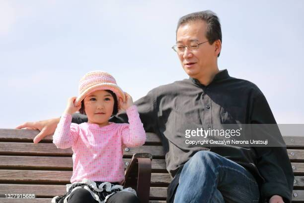 father and child sitting together on a bench outdoor - saitama prefecture stock pictures, royalty-free photos & images
