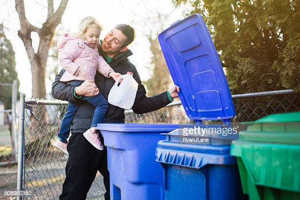 father and child taking out recycle trash - garbage can stock photos and pictures