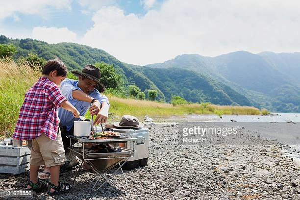 Father and child to a barbecue by the lake