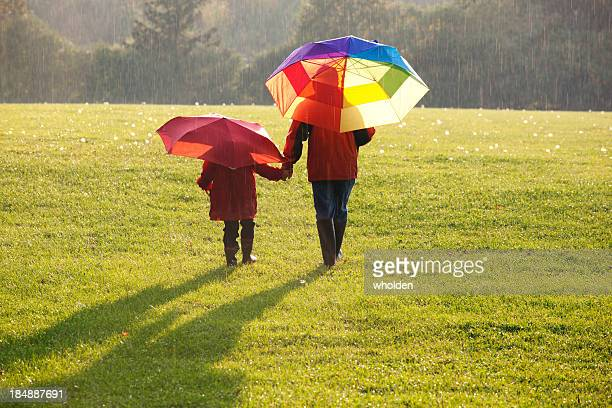 Father and child walking in a field in rain with umbrellas