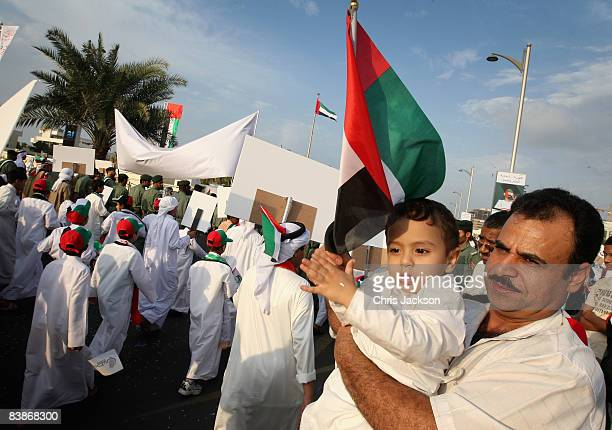 A father and child watch the Dubai National Day parade on December 1 2008 in Dubai United Arab Emirates National Day festivities traditionally take...