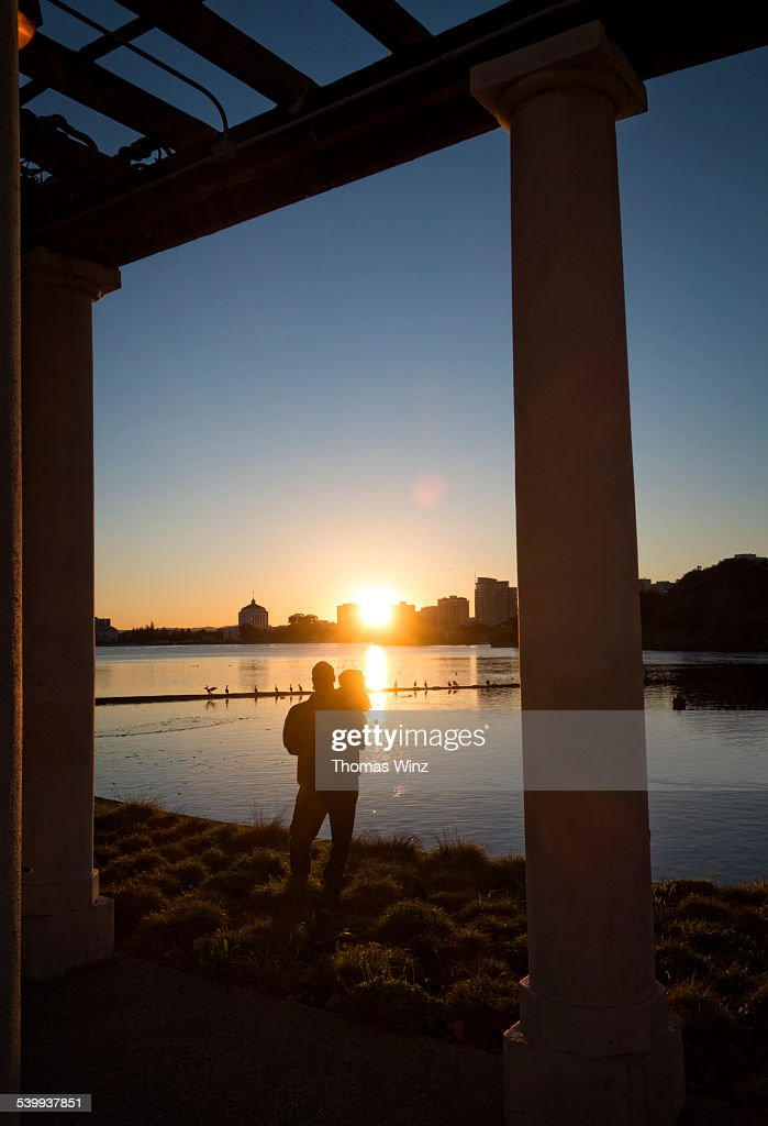Father and child watching sunset : Stock Photo