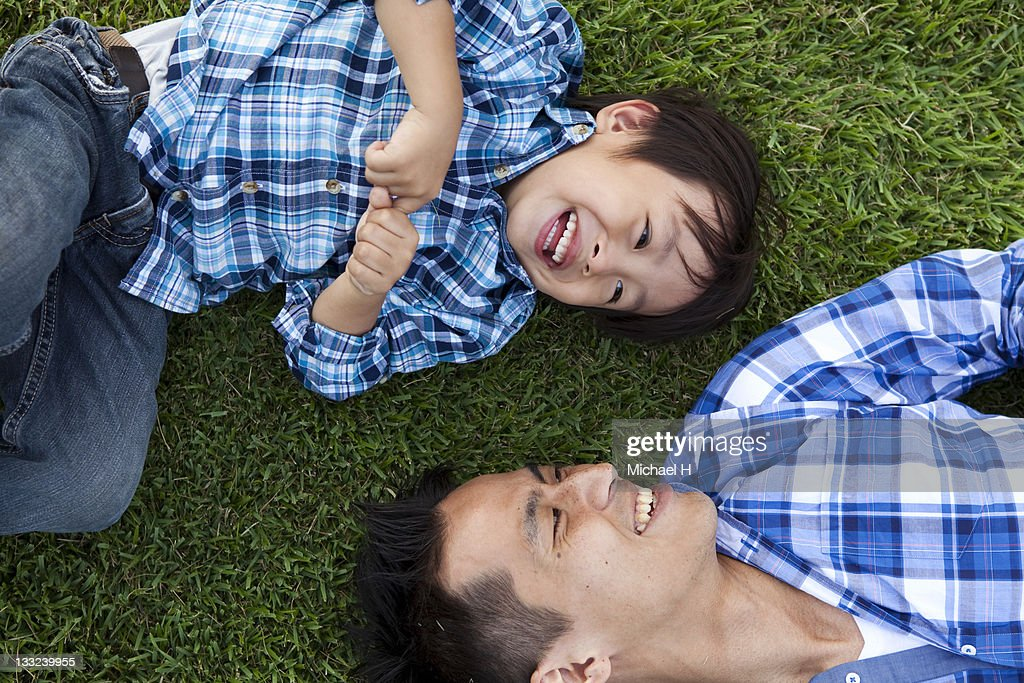 Father and child who have lain down on the lawn : Stock Photo