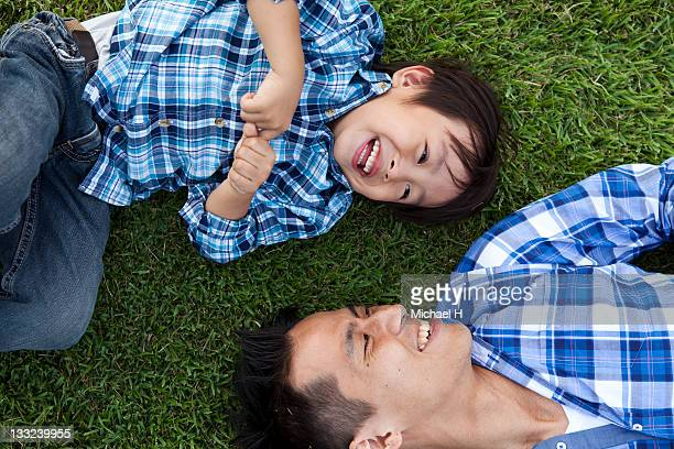 Father and child who have lain down on the lawn