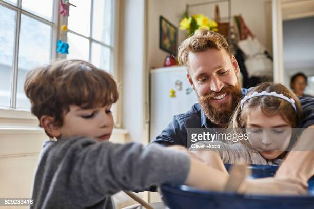 Father and children baking at home