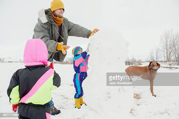 Father and children building snowman