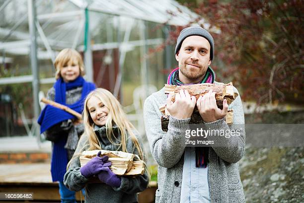 Father and children carrying logs
