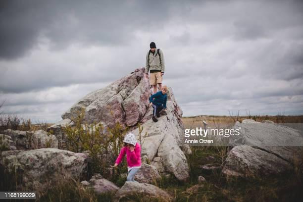 father and children climb on a large prairie rock - rock object photos et images de collection