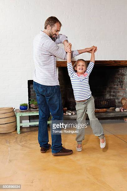 Father and children dancing in living room