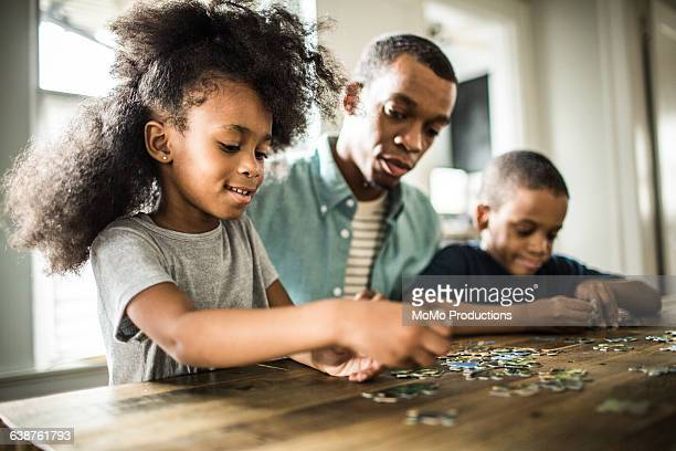 father and children doing puzzle - puzzle stock pictures, royalty-free photos & images