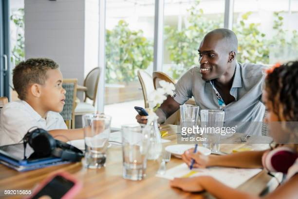 Father and children eating in restaurant