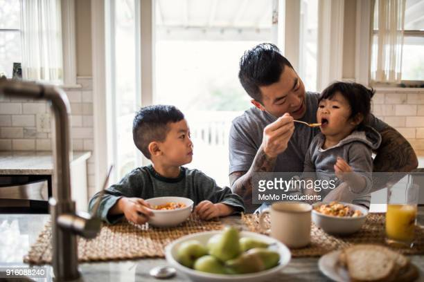 Father and children having breakfast in kitchen