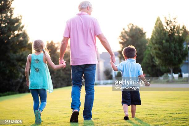 Father and Children holding Hands Walking in Park