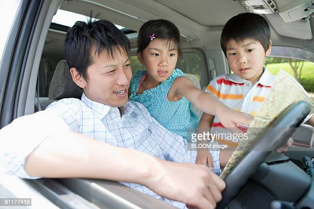 Father and children in car, looking at map
