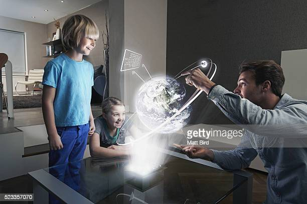 Father and children looking at 3d projection of the Earth
