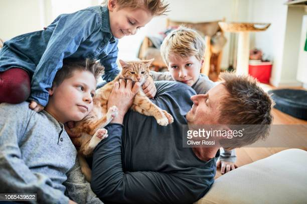 father and children lying down at home with cat - cat family stock photos and pictures