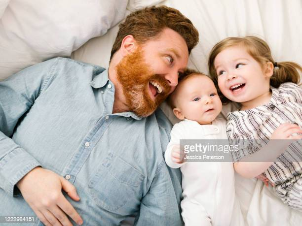 father and children (2-3 months, 2-3) lying on bed and laughing - baby boys stock pictures, royalty-free photos & images