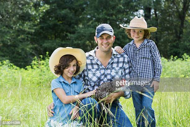 Father and children on family farm holding a chicken
