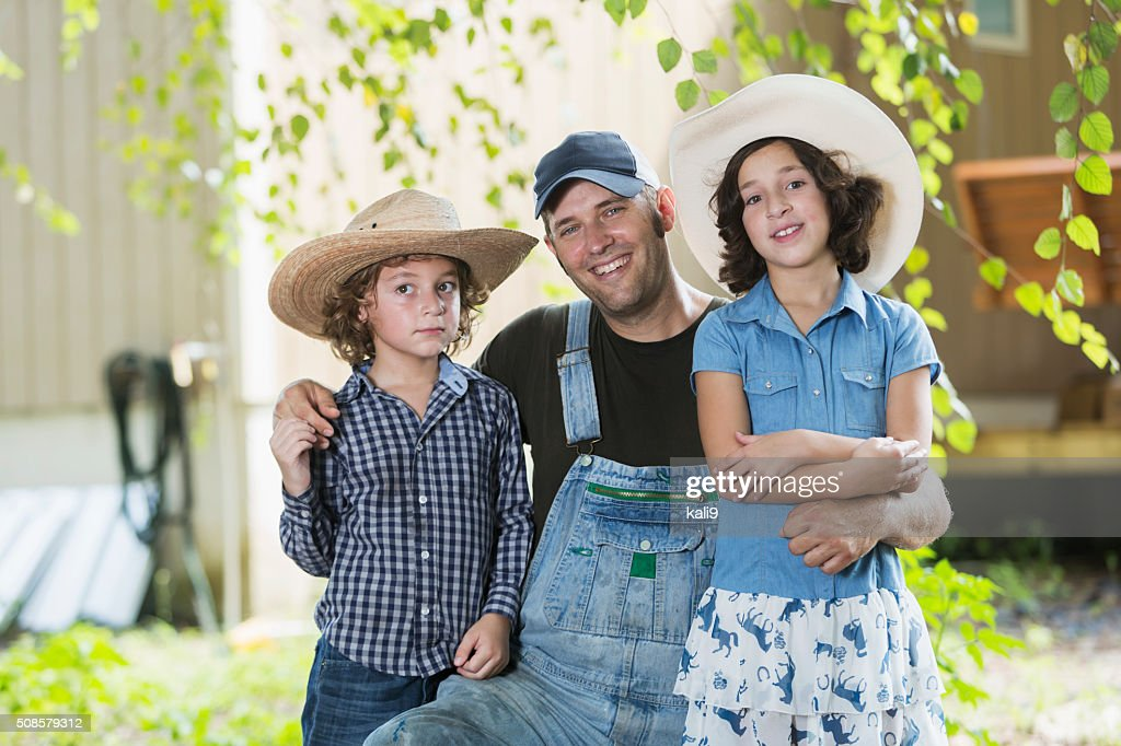 Father and children on family farm smiling at camera : Stockfoto