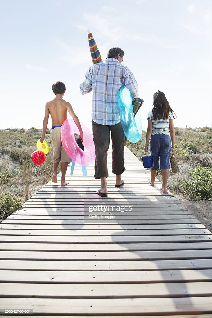 Father and children (7-9) on path carrying beach toys, rear view : Stock Photo