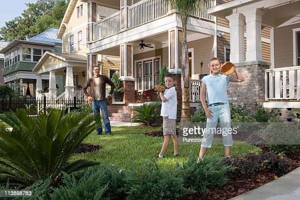 Father and children playing catch in front yard