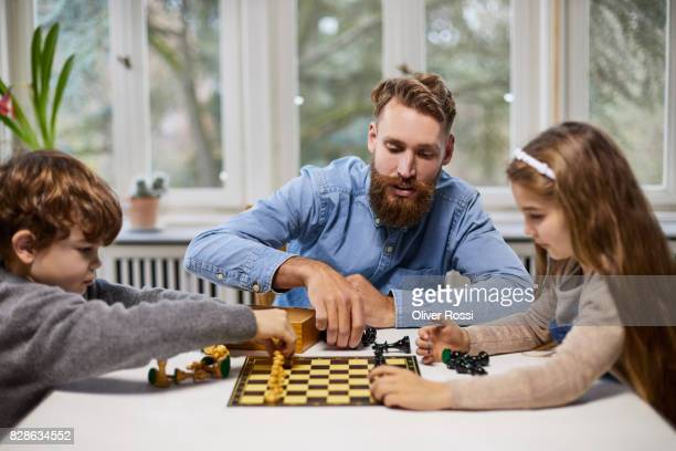 Father and children playing chess at home