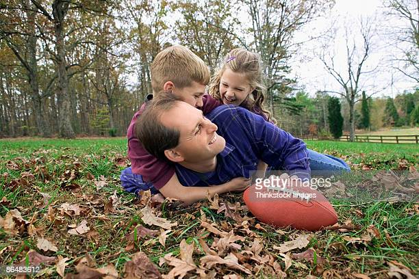 Father and children playing football