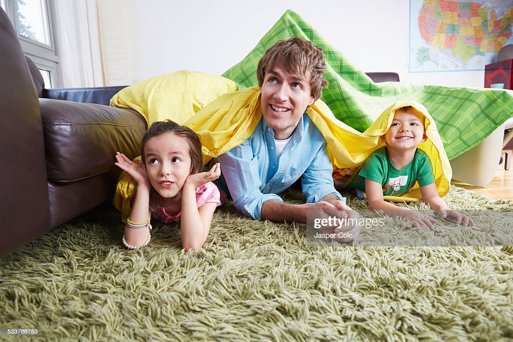 Father and children playing in blanket fort in living room : Stock Photo