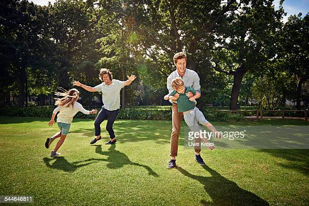 Father and children playing in park