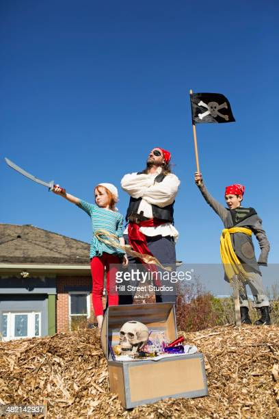 Father and children playing in pirate costumes outdoors