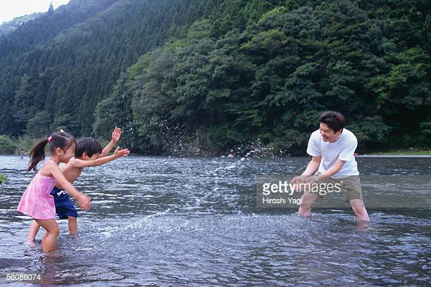 Father and children playing in river