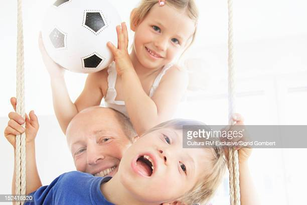 father and children playing on swing - sigrid gombert stock pictures, royalty-free photos & images
