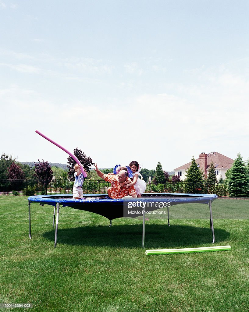 Father and children (2-8) playing on trampoline on lawn : Stock Photo