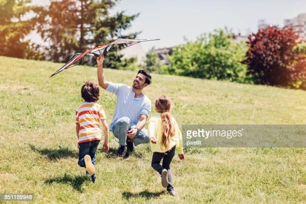 pai e filhos a brincar com a pipa - releasing - fotografias e filmes do acervo