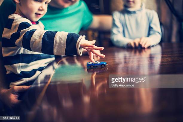 Father and children playing with a toy car