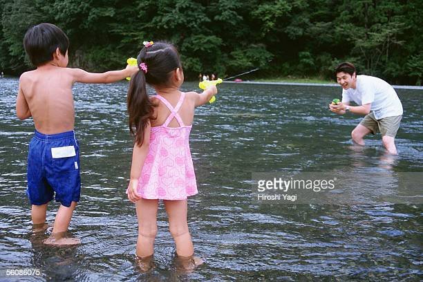 Father and children playing with squirt guns