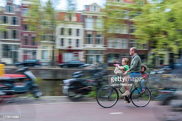 Father and children, riding their bike through the streets of Amsterdam, The Netherlands