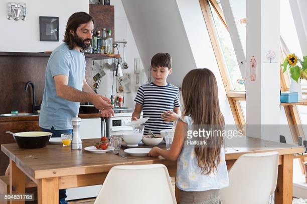 Father and children setting table for lunch in kitchen