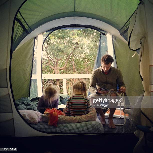 Father and children sitting inside tent