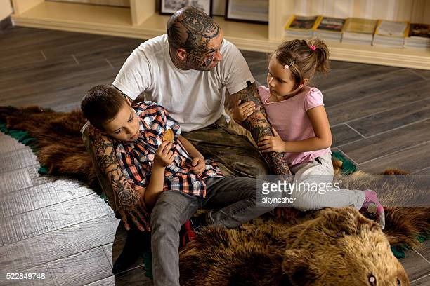 father and children sitting on the carpet and communicating. - animal skin rug stock pictures, royalty-free photos & images