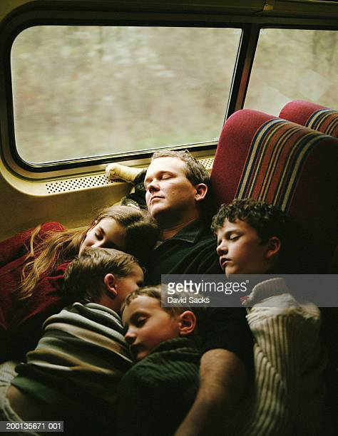 Father and children (4-10) sleeping on train