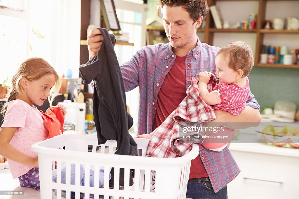 Father And Children Sorting Laundry In Kitchen : Stock Photo