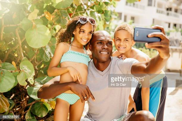 Father and children taking selfie with cell phone outdoors