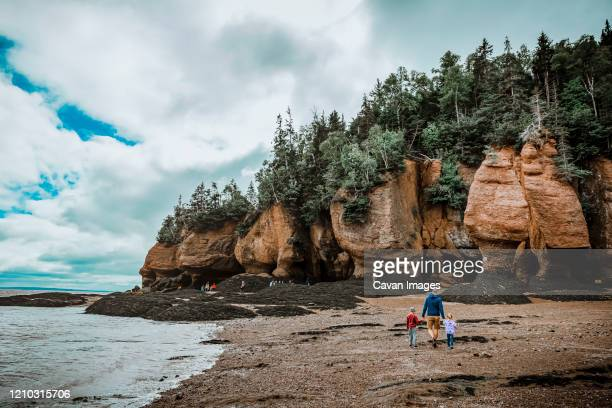 father and children walking by the river on a cloudy day - new brunswick canada stock pictures, royalty-free photos & images